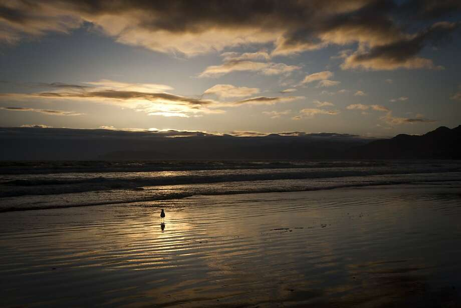 The sunset lights up the sky  and reflects off the water at Pismo Beach. Photo: Ali Thanawalla, SFGate