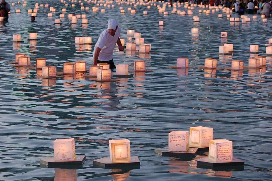 The 2011 Lantern Floating Hawai'i will feature more than 3,000 lanterns in response to increased demand after the Northern Japan castastrophe. Here, a 2010 volunteer helpskeep a lantern on track. Photo: Jeanne Cooper, Special To SFGate