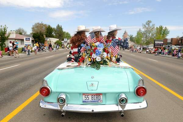A trio of local area rodeo queens ride in the backseat of a 1955 Ford Thunderbird during the Parade America on Saturday, May 21, 2011 in Nampa, Idaho.