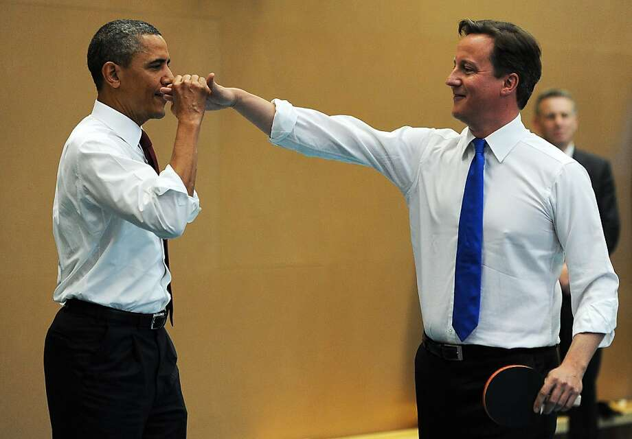 US President Barack Obama (L) high-fives with British Prime Minister David Cameron (R) as they play table tennis with students of the Globe Academy school in London, on May 24, 2011. Photo: Jewel Samad, AFP / Getty Images