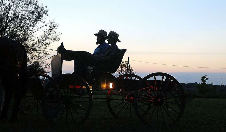 In a May 24, 2011 photo, Amish men stop to speak with neighbors while traveling home at dusk in their buggy near Maysville, Ky. Photo: Terry Prather, The Ledger Independent