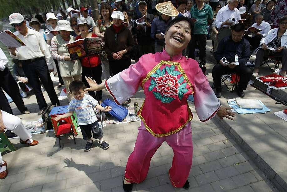 A Chinese woman dances as a group of people sing revolutionary songs at a park in Beijing Wednesday, May 25, 2011. Photo: AP