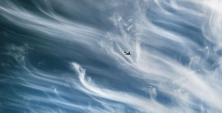 "A plane flies over central London in a sky covered by cirrus clouds as the Icelandic ash cloud moved away from British skies, Wednesday May 25, 2011. High levels of volcanic ash could return to the United Kingdom on Friday just as the bank holiday weekend getaway begins, forecasters have warned. Volcano experts in Iceland said the eruption appeared to be tapering off. Observers at the crater were reporting only steam, said Pall Einarsson, from the University of Iceland.  ""The worst is over,"" said Icelandic Prime Minister Johanna Sigurdardottir in a statement, after touring the region around Grimsvotn on Tuesday. Photo: Lewis Whyld, AP"