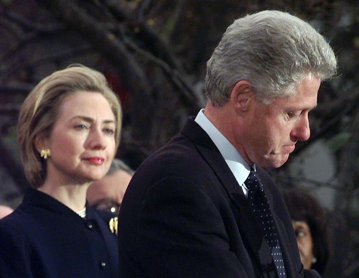 """First lady Hillary Rodham Clinton watches President Clinton pause as he thanks those Democratic members of the House of Representatives who voted against impeachment in this Dec. 19, 1998 file photo. Her husband's dalliances with Monica Lewinsky left Americans baffled, and at the same time admiring, that Hillary would stand by her husband. """"The most difficult decisions I have made in my life were to stay married to Bill, and to run for the Senate from New York,"""" she said. She decided she wanted the marriage to last, if that was possible. (AP Photo/Susan Walsh, File)"""