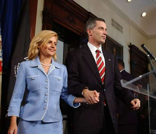 New Jersey Gov. James E. McGreevey, right, holds his wife Dina Matos McGreevey's hand, before announcing he will resign, during a news conference at the Statehouse in Trenton, N.J., Thursday, Aug. 12, 2004. In a stunning declaration, McGreevey announced his resignation Thursday and acknowledged that he had an extramarital affair with another man. The Democrat said his resignation would be effective Nov. 15. (AP Photo/Brian Branch-Price) Photo: Brian Branch Price, AP