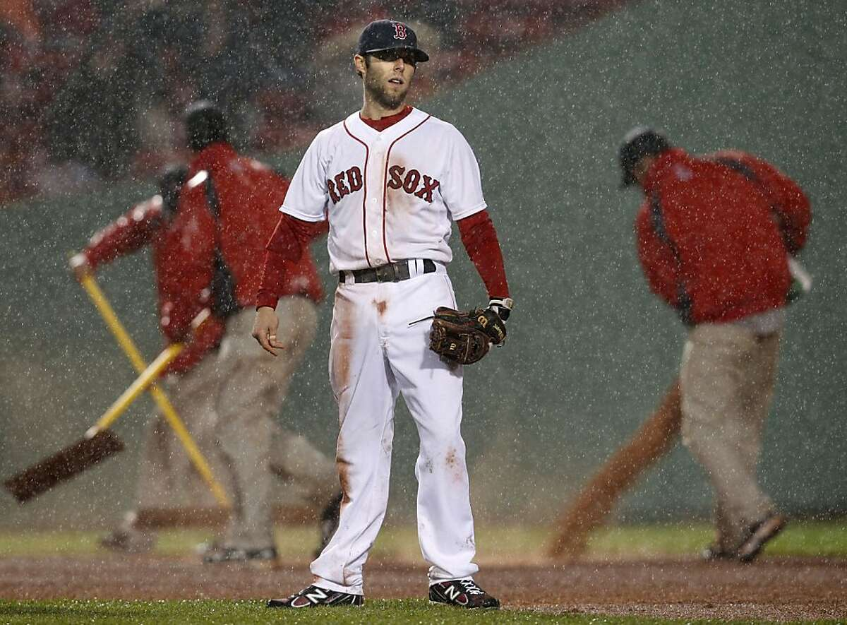 Boston Red Sox second baseman Dustin Pedroia stands in the infield as grounds crew rake and pour dirt just before a rain delay in the eighth inning of a baseball game against the Detroit Tigers at Fenway Park in Boston Wednesday, May 18, 2011.