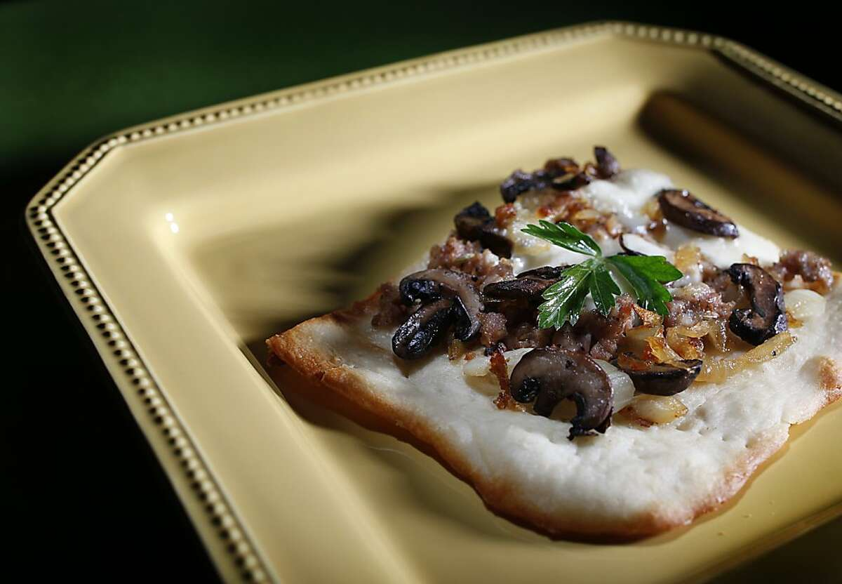 Sausage, mushroom and caramelized onion pizza sits on a plate, Wednesday, Oct. 6, 2010 in San Francisco, Calif.