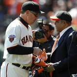 Giants great Willie Mays (right) presents the World Series championship banner to manager Bruce Bochy before the Giants' home opener against the St. Louis Cardinals at AT&T Park in San Francisco on Friday.