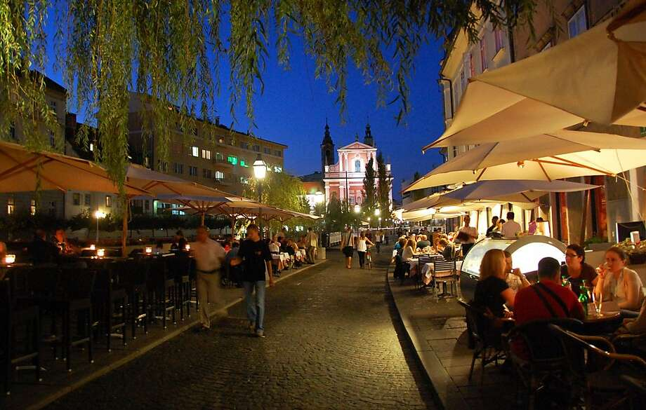 Ljubljana's riverfront promenade is lined with quaint boutiques, great restaurants, and cafes ripe for people-watching. Photo: Cameron Hewitt