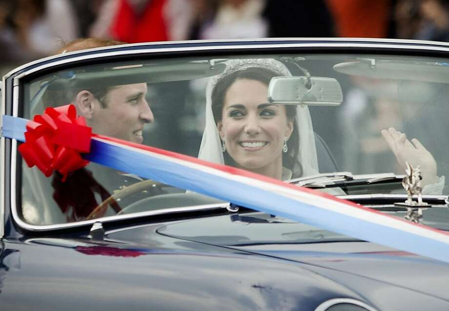 Britain's Prince William drives his wife Kate, Duchess of Cambridge, away from Buckingham Palace in a vintage Aston Martin Volante convertible after their wedding at London's Westminster Abbey, Friday, April, 29, 2011. Photo: Daniel Ochoa De Olza, AP