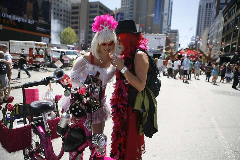 A woman blows bubbles as she rides her bicycle around the 12th annual How Weird Street Faire on Howard Street in San Francisco on Sunday. Photo: Anna Vignet, The Chronicle