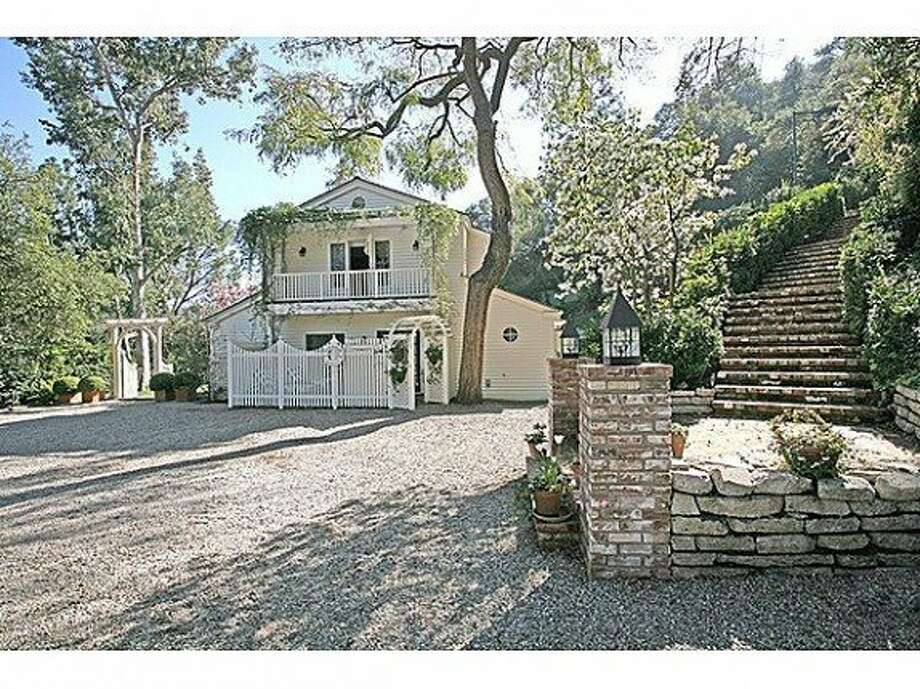 A pea gravel driveway and winding stairway greet you at the entrance of the home. Photo: Prudential California Realty