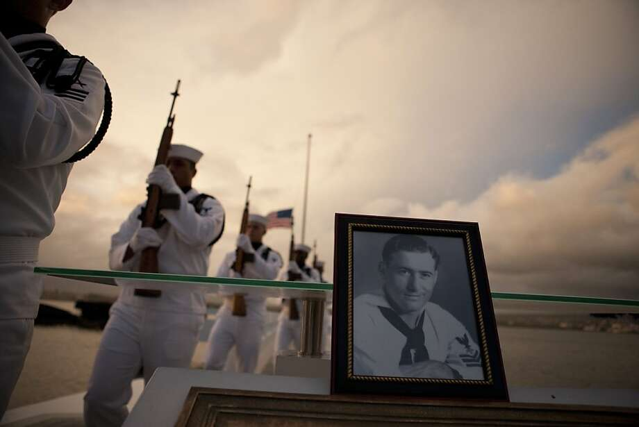 Navy Region Hawaii Honor Guard march past a photograph of Pearl Harbor survivor Lee Soucy during the internment ceremony for Soucy, Tuesday, Dec. 6, 2011 in Honolulu. Soucy, who died last year at the age of 90, wanted to have his ashes interred inside the USS Utah, his ship that sank during the surprise Japanese attack on Pearl Harbor in Dec. 7, 1941. (AP Photo/Marco Garcia) Photo: Marco Garcia, AP