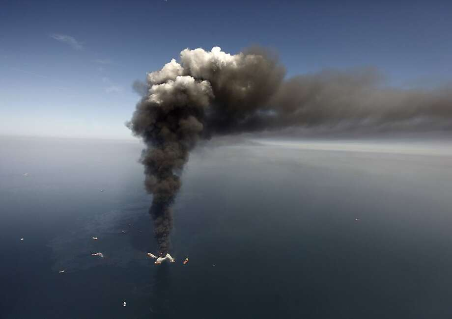 This Wednesday, April 21, 2010 file photo shows oil in the Gulf of Mexico, more than 50 miles southeast of Venice on Louisiana's tip, as a large plume of smoke rises from fires on BP's Deepwater Horizon offshore oil rig. An April 20, 2010 explosion at the offshore platform killed 11 men, and the subsequent leak released an estimated 172 million gallons of petroleum into the gulf. Photo: Gerald Herbert, AP