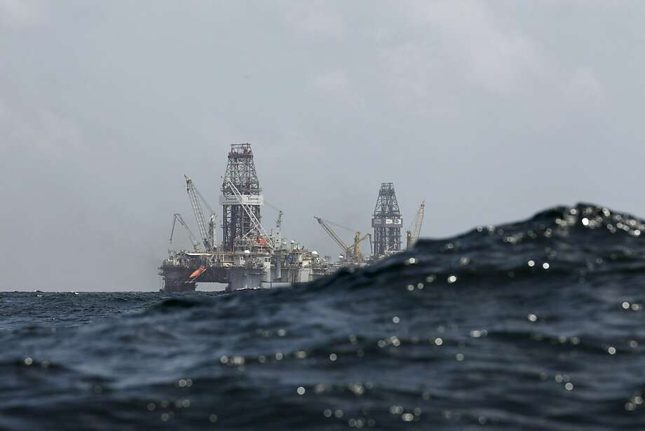 In this Thursday, July 22, 2010 file picture, a swell partially obscures the Development Driller II, left, and Development Driller III, which are drilling the relief wells, at BP's Deepwater Horizon oil spill site in the Gulf of Mexico off the Louisiana coast. An April 20, 2010 explosion at the offshore platform killed 11 men, and the subsequent leak released an estimated 172 million gallons of petroleum into the gulf. Photo: Gerald Herbert, AP