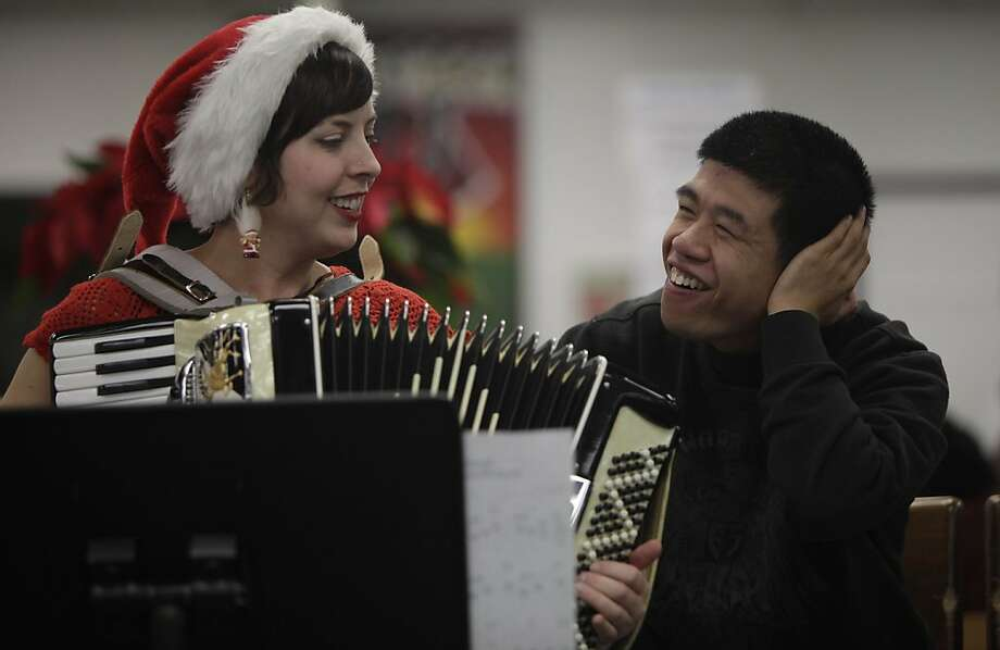 Heidi Hubrich (l to r), SPED transition teacher, and Ryan Lai, Community Access Transition student, sing together as they host a holiday sing-a-long with their class in the Library at Ruth Asawa School of the Arts on Tuesday, December 6, 2011 in San Francisco, Calif. The Community Access Transition classs in Room 208 at Ruth Asawa School of the Arts hosted a holiday sing-a-long to celebrate San Francisco Inclusive Schools week . Ran on: 12-07-2011 Teacher Heidi Hubrich and student Ryan Lai take part in a holiday sing-along with their special education class Tuesday in the Ruth Asawa School of the Arts library as part of Inclusive Schools Week. Photo: Lea Suzuki, The Chronicle
