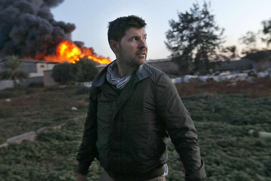 Getty Images photographer Chris Hondros stands in front of a burning building while on assignment on April 18, 2011, in Misrata, Libya. Hondros was gravely injured on April 20, 2011 when a rocket-propelled grenade (RPG) struck a house he was in. Photo: Getty Images