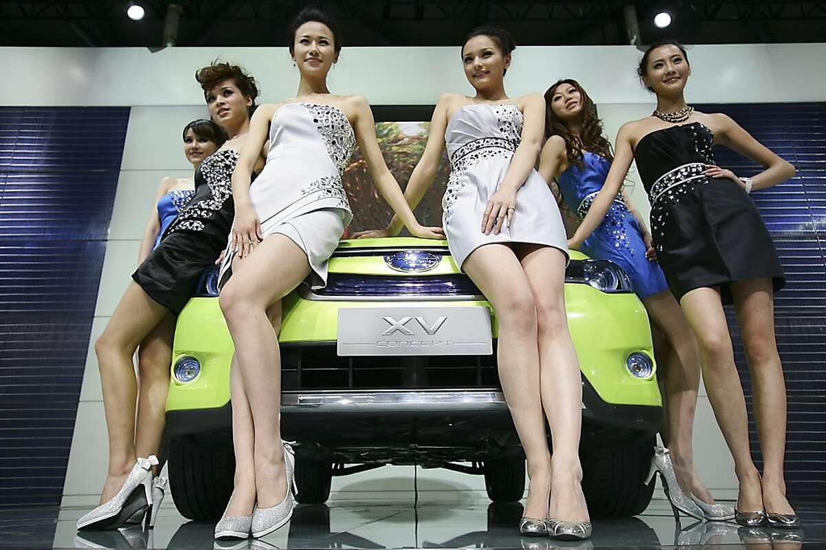 Models sit on a Subaru's XV concept car to pose for photographers at Subaru presentation section on the press day at the Shanghai International Auto Show Tuesday, April 19, 2011 in Shanghai, China.