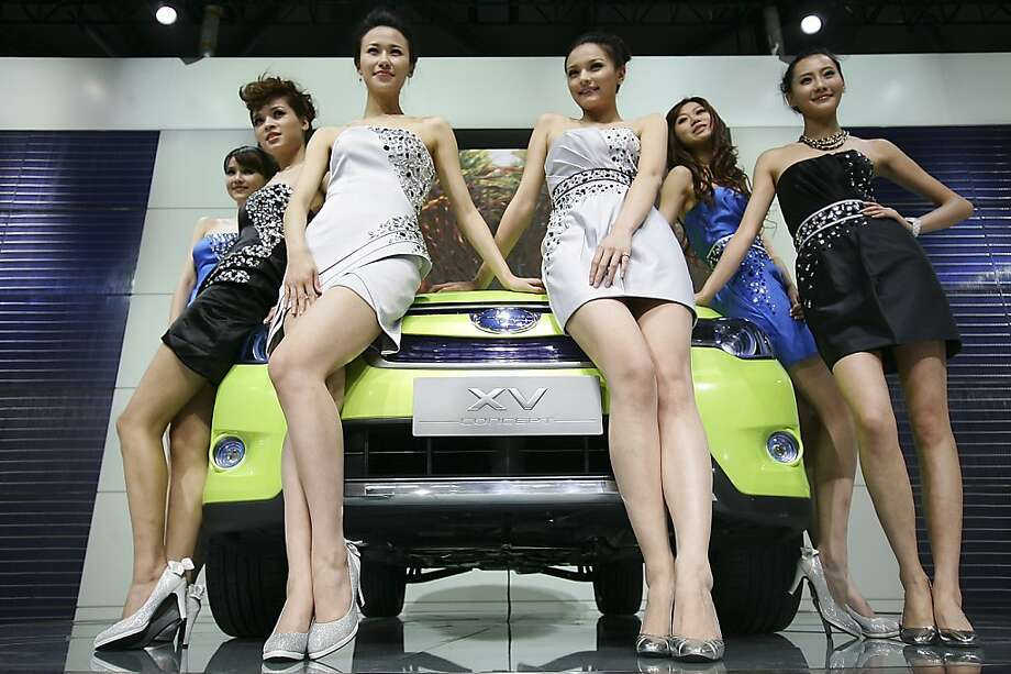 Models sit on a Subaru's XV concept car to pose for photographers at Subaru presentation section on the press day at the Shanghai International Auto Show Tuesday, April 19, 2011 in Shanghai, China. Photo: Str, AP