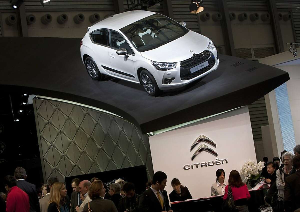 A Citroen DS4 car model is displayed on top of a counter while workers serve for invited journalists and guests during the press day at the Shanghai International Auto Show in Shanghai, China Tuesday, April 19, 2011. Global automakers unveiled ambitious expansion plans for China on Tuesday, targeting the country's newly prosperous drivers as the industry struggles to recover from Japan's tsunami.