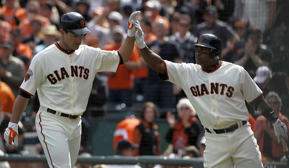 Pat Burrell is greeted by Miguel Tejada after Burrell's solo blast in the sixth inning of the Giants' home opener against the St. Louis Cardinals at AT&T Park in San Francisco on Friday. Photo: Paul Chinn, The Chronicle