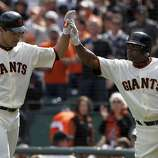 Pat Burrell is greeted by Miguel Tejada after Burrell's solo blast in the sixth inning of the Giants' home opener against the St. Louis Cardinals at AT&T Park in San Francisco on Friday.