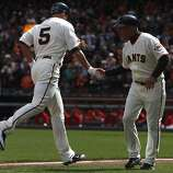 Pat Burrell is greeted by Tim Flannery after Burrell's solo blast in the sixth inning of the Giants' home opener against the St. Louis Cardinals at AT&T Park in San Francisco on Friday.