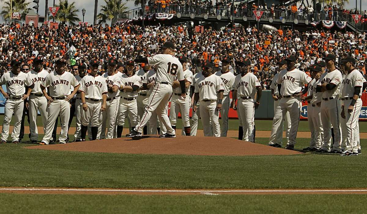 Giants pitcher Matt Cain throws out the ceremonial first pitch with the starting lineup behind him as the San Francisco Giants prepare for their home opener against the St. Louis Cardinals at AT&T Park on Friday.