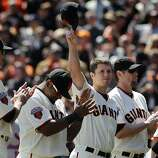 Buster Posey tips his cap as he's introduced at the Giants' home opener against the St. Louis Cardinals at AT&T Park in San Francisco on Friday.