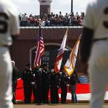 An SFPD color guard carries the stars and stripes before the Giants' home opener against the St. Louis Cardinals at AT&T Park in San Francisco on Friday.