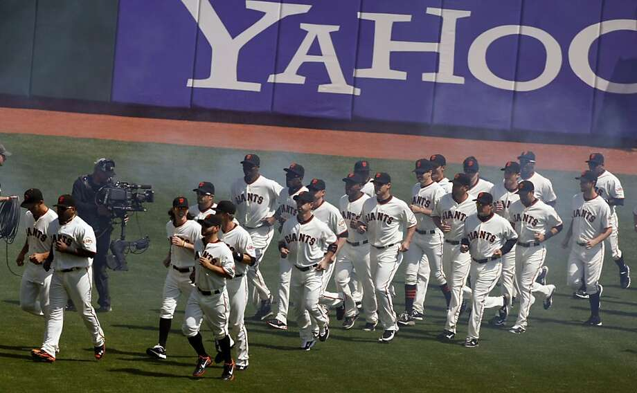 The San Francisco Giants run onto the field during the Opening Day pregame celebration Friday that honored the team for winning the World Series. Photo: Lance Iversen, The Chronicle
