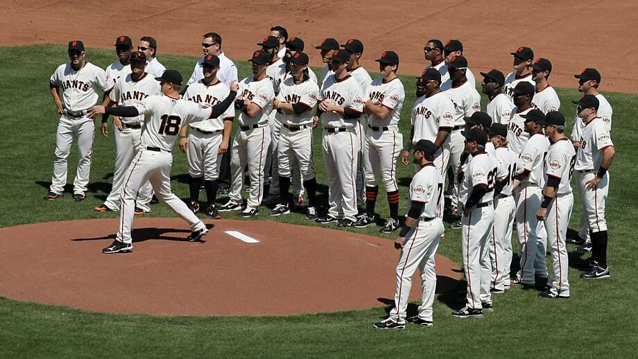 San Francisco Giants pitcher Matt Cain is surrounded by his teammates as he throws out the first pitch during Opening Day ceremonies prior to the game with the St. Louis Cardinals on Friday. Photo: Lance Iversen, The Chronicle