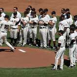 San Francisco Giants pitcher Matt Cain is surrounded by his teammates as he throws out the first pitch during Opening Day ceremonies prior to the game with the St. Louis Cardinals on Friday.