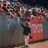 Sergio Romo hand delivers a baseball to fans leaning over the left field fence during batting practice before the Giants' home opener against the St. Louis Cardinals at AT&T Park in San Francisco on Friday.