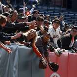 Fans lunge for a loose ball tossed into the stands by Sergio Romo before the Giants' home opener against the St. Louis Cardinals at AT&T Park in San Francisco on Friday.