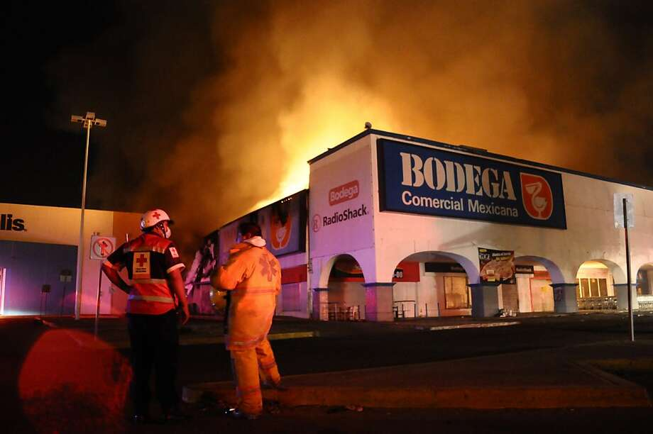 Firefighters and first responders stand in front of a burning supermarket after gun-battle between soldiers and gunmen in the resort city of Acapulco, Mexico, Monday April 4, 2011. The Public Safety Department in Guerrero state says a soldier and two gunmen were killed in the clash that also destroyed a supermarket, a movie complex and stores in a shopping center. Photo: Bernandino Hernandez, AP
