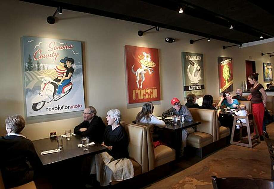 The walls of Rosso are decorated with original poster art. Tables and booths are both available. Rosso Pizzeria and Wine Bar is located at 53 Montgomery Drive in Santa Rosa. Photo: Brant Ward, The Chronicle