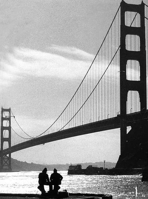 Jan 9, 1975 - Afternoon sunshine at Ft. Baker as two fisherman fish for crab on a dock with the Golden Gate Bridge in the background. Photo: Susan Ehmer, The Chronicle