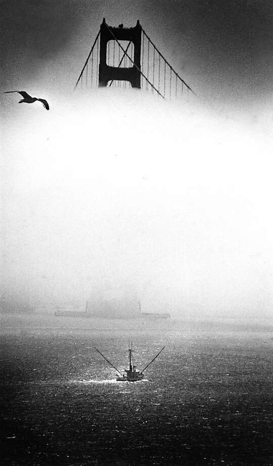 August 8, 1984 - Fog comes in with a fishing boat slipping out under it through the Golden Gate. Photo: Eric Luse, The Chronicle