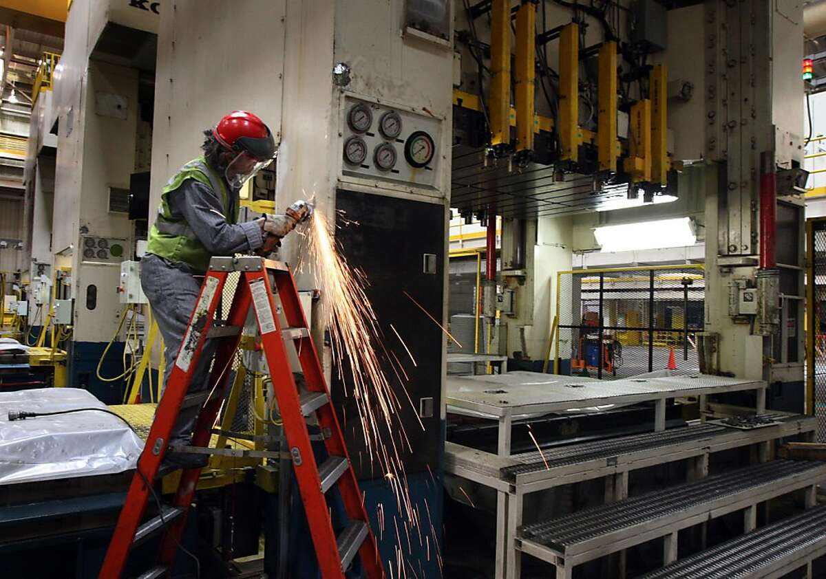 Alexander Batticelli from Fremont, prepares a press for fresh paint as Tesla Motors, maker of electric cars prepares the old Nummi factory in Fremont California for the production of Tesla new Model S. electric car that should be in showrooms in mid year 2012. Wednesday June 22, 2011