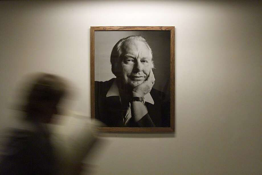 A student reading a booklet passes by one of the many large poster-sized photographs of Ron Hubbard, the founder of Scientology, at American St. Hill Organization, the Scientology headquarters in Los Angeles. Photo: Deanne Fitzmaurice, The Chronicle 2001