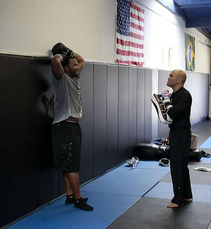 Marcel Reece, takes a break while working with his instructor Allan Maravilla during an exercise as the Oakland Raider fullback works out at Crispim Brazilian Jiu-Jutsu in Pleasanton, Ca. on Tuesday June 14, 2011. Reece keeps in shape during the NFL off season with daily workouts at the center. Photo: Michael Macor, The Chronicle