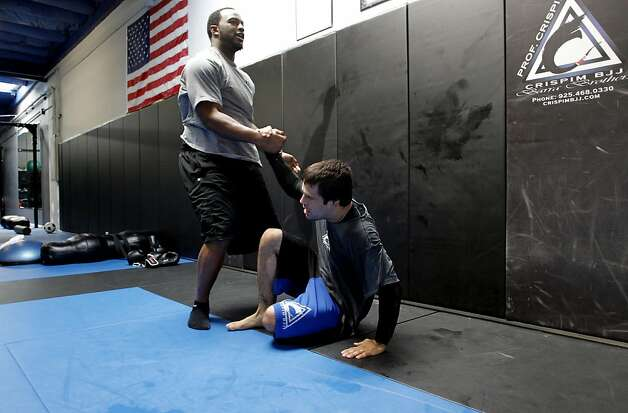 Marcel Reece, lends a hand to his instructor Alexander Crispim during an exercise as the Oakland Raider fullback works out at Crispim Brazilian Jiu-Jutsu in Pleasanton, Ca. on Tuesday June 14, 2011. Reece keeps in shape during the NFL off season with daily workouts at the center. Photo: Michael Macor, The Chronicle