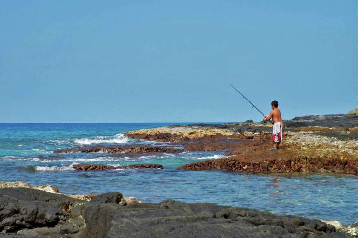 """A boy fishes on the Big Island near Ho'okena Beach, not far from the City of Refuge. The photo, taken by Elisabeth Levy, is among those that will be be shown as part of """"Mahalo Hawaii,"""" a photography show set for Jan. 8, from 3-7 p.m., at 24 Clapboard Ridge Road in Danbury."""