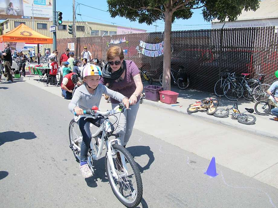 Jess Zak teaches Emma Cooney Geisler to ride a bike. Photo: San Francisco Bicycle Coalition