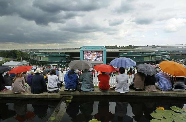 Spectators shelter under umbrellas as they watch the semifinal between Russia's Maria Sharapova and Germany's Sabine Lisicki on the grounds of Wimbledon on a giant screen at the All England Lawn Tennis Championships at Wimbledon, Thursday, June 30, 2011. Photo: Kirsty Wigglesworth, AP