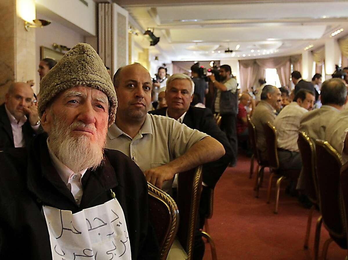 Muslim cleric Jodat Said (L) holds a sign which says in Arabic, There is an Arab solution in which nobody loses