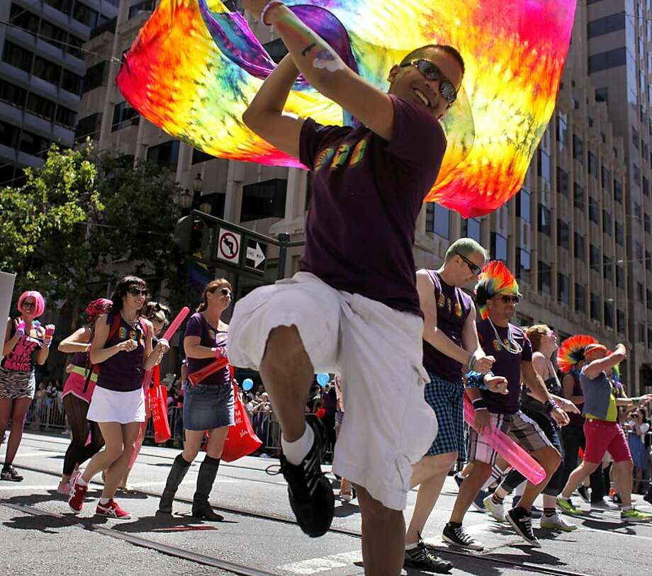 """Vernon Magsino dances with a rainbow flag as he marches down Market Street with the Virgin Airlines contingent in San Francisco Pride Parade, Sunday June 26, 2011, in San Francisco, Calif. The 41st Pride celebration and parade carried the theme of """"In Pride We Trust"""" ,to commemorate and celebrate the history, culture and striving for equal rights. Photo: Lacy Atkins, The Chronicle"""