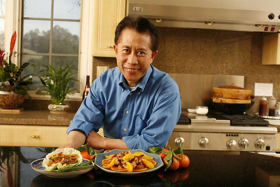 Martin Yan, cookbook author and on tv cooking shows. He has a new cooking book coming out.  Photo of Martin Yan in his kitchen with two of his dishes, Rainbow Stir Fry (left) and Tangerine Peel Chicken (right). photo by Craig Lee / The Chronicle Photo: Photo By Craig Lee, SFC
