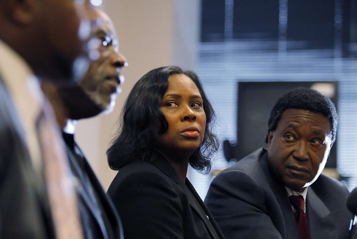 Wanda Johnson, center, listens to her brother, Cephus Johnson, speak to the media about the Oscar Grant Foundation during a press conference. Johnson's attorney, John Burris, is seated at right. Wanda Johnson, mother of Oscar Grant, settled with BART over her son's shooting for $1.3 million on Tuesday, June 28, 2011. The settlement was announced at the office of her lawyer, John Burris, in Oakland, Calif.